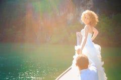 Blonde Braut und hübscher Bräutigam auf Boot Stockfotos