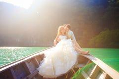 Blonde Braut und hübscher Bräutigam auf Boot Lizenzfreie Stockfotografie