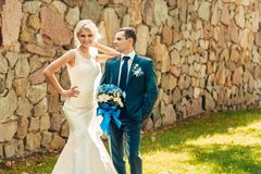 Blonde Braut und ihr Bräutigam stehen auf dem Gras in einem exotischen Park Lizenzfreies Stockbild