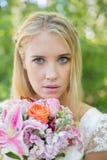 Blonde Braut, welche die Kamera hält Blumenstrauß betrachtet Stockbild