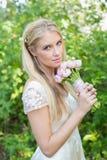 Blonde Braut, welche die Kamera hält rosa Blumenstrauß betrachtet Lizenzfreies Stockfoto