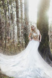 Blonde bride angel in long white skirt standing in sunny forest Stock Photography