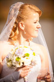 Blonde bride at autumn park looking at sun Royalty Free Stock Photography