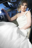 Blonde bride in a car Stock Images