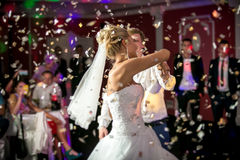 Blonde bride dancing at restaurant in flying confetti Stock Images