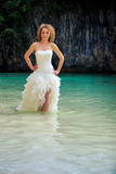 Blonde bride in fluffy hands on waist in shallow azure sea Royalty Free Stock Photos