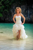 Blonde bride in fluffy hands on waist in shallow azure sea Royalty Free Stock Images