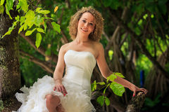 Blonde Bride In Fluffy Dress Sits On Trunk Groom Stands Near Stock Photos