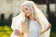 Blonde bride in lace dress backgroung wall in garden. Gently blonde bride in lace dress backgroung wall in garden Royalty Free Stock Image