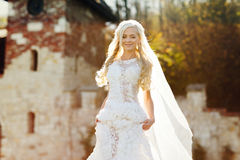 Blonde bride in lace dress backgroung wall in garden. Gently blonde bride in lace dress backgroung wall in garden Royalty Free Stock Photos