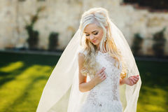 Blonde bride in lace dress backgroung wall in garden Stock Photo