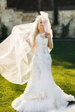 Blonde bride in lace dress backgroung wall in garden. Gently blonde bride in lace dress backgroung wall in garden Stock Images