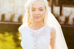 Blonde bride in lace dress backgroung wall in garden. Gently blonde bride in lace dress backgroung wall in garden Royalty Free Stock Images