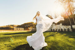 Blonde bride in lace dress backgroung wall in garden. Gently blonde bride in lace dress backgroung wall in garden Stock Photo