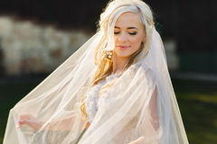 Blonde bride in lace dress backgroung wall in garden. Gently blonde bride in lace dress backgroung wall in garden Royalty Free Stock Photo