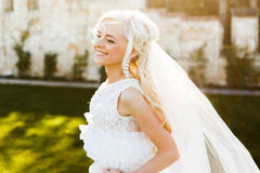 Blonde bride in lace dress backgroung wall in garden Royalty Free Stock Image