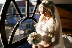 Blonde bride in lace dress backgroung wall in garden Royalty Free Stock Photo