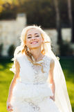 Blonde bride in lace dress backgroung wall in garden Royalty Free Stock Images