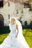 Blonde bride in lace dress backgroung wall in garden Stock Photos