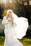 Blonde bride in lace dress backgroung wall in garden Royalty Free Stock Photography