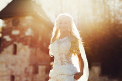 Blonde bride in lace dress backgroung wall in garden Royalty Free Stock Photos