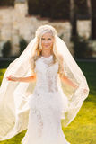 Blonde bride in lace dress backgroung wall in garden Stock Image