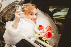 Blonde bride looking out of limousine window Royalty Free Stock Photos