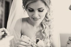 Blonde bride looks on flowers.  stock photo
