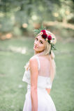 Blonde bride looks over her tender shoulder while posing royalty free stock image