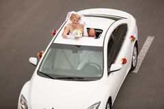 Blonde bride popping out of car sunroof Royalty Free Stock Photography