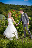 Blonde bride pulling groom by hand at park Stock Images