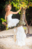 Blonde bride sit on tree Royalty Free Stock Image