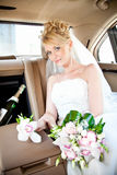 Blonde bride sitting on backseat of luxurious car Royalty Free Stock Photos