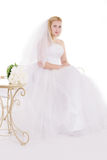 Blonde bride sitting with bouquet Stock Photo