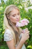 Blonde bride smelling her bouquet Stock Photos