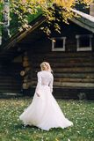 Blonde bride is walking in fluttering dress on wooden house background. Back view. Artwork. Blonde bride is walking in fluttering dress on wooden house royalty free stock photos