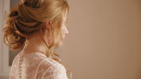 The blonde bride in a wedding dress with flowers posing for the camera stock footage