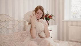Blonde bride in negligee looks and hugs teddy bear stock video footage