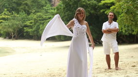 Blonde Bride in White Wedding Dress Stand in front of Young Groom. Blonde bride swinging wings of wedding dress standing in front of groom on jungle beach in stock video footage