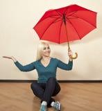Blonde brillante con un paraguas rojo que se sienta en el piso en el cuarto Foto de archivo