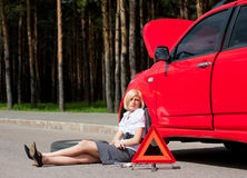 Blonde and broken car Stock Photos