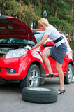 Blonde and broken car. Blonde changing tire alone on a road Stock Photos