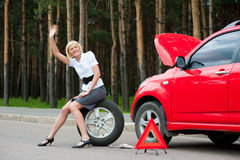 Blonde and broken car. Blonde girl asks for help on the road near her broken car Royalty Free Stock Photos