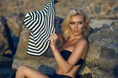 Blonde bronceado magnífico en el traje de baño que la inclina detrás contra las piedras grandes en la playa y que mira a un lado imagen de archivo libre de regalías