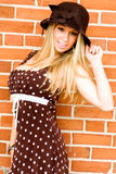 Blonde in brown dress and hat Royalty Free Stock Photography