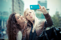 Blonde and brunette beautiful stylish young women Stock Photos