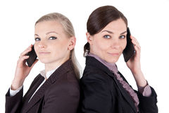 Blonde and brunette business woman with phone stock image