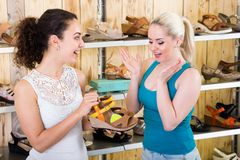 Blonde and brunette buy summer shoes in the modern store royalty free stock images