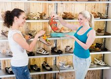 Girl seller helps blonde girl with a selection of summer shoes stock images
