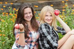 Blonde and brunette eating ripe apples Royalty Free Stock Photos